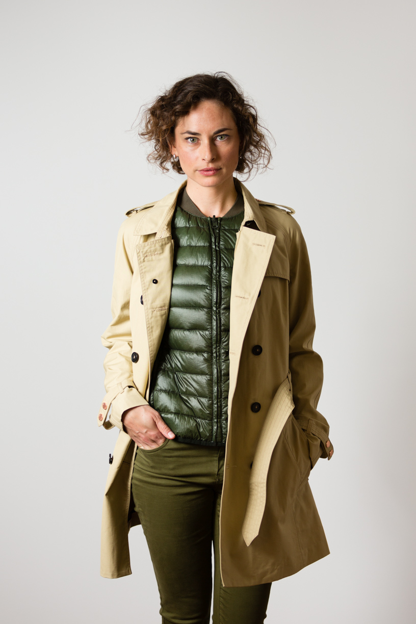 Katharina wearing the British Millerain Trench Coat over a forrest green goose down liner vest
